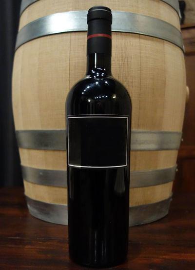 Close-up of wine bottle against barrel