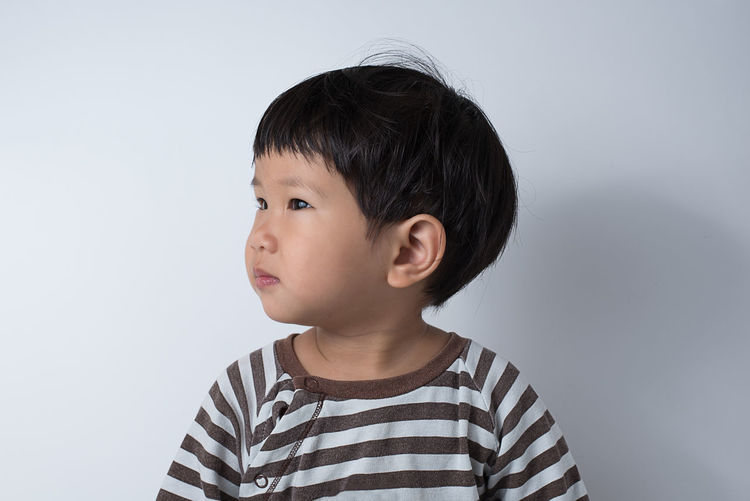 Cute boy looking away against white background