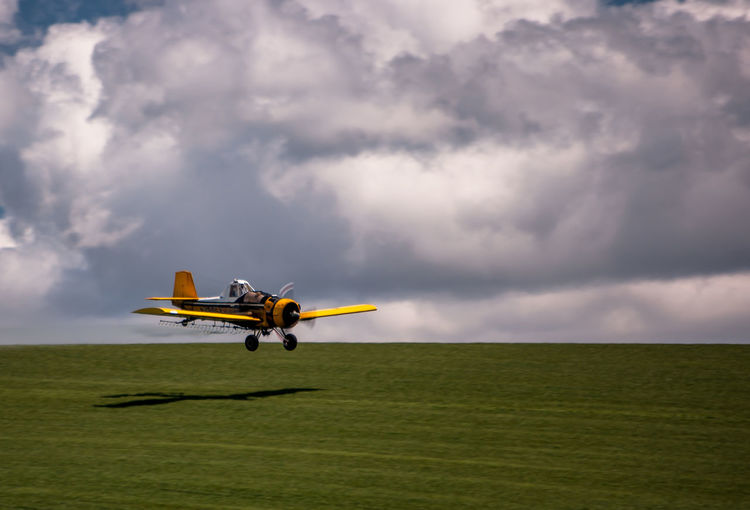 Biplane Flying Above Grassy Field Against Cloudy Sky