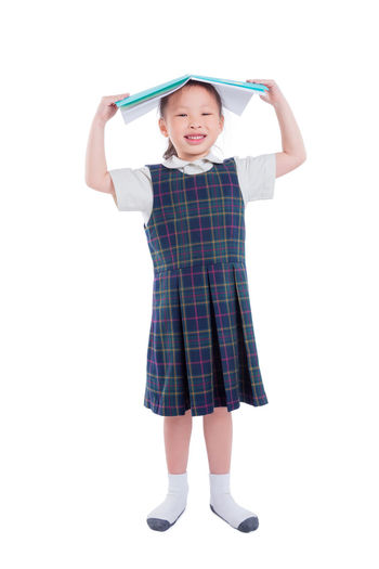 School Uniform Girl Isolated White Kid Child SchoolGirl Background Young Student Education Study Beautiful Dress Pretty Learn Smart Happy Portrait Cute Little Kindergarten Studio Looking Posing Knowledge Female person One Smile Body Youth Pose STAND Enjoy Schoolkid Book Reading Asian  Chinese Full Length Holding