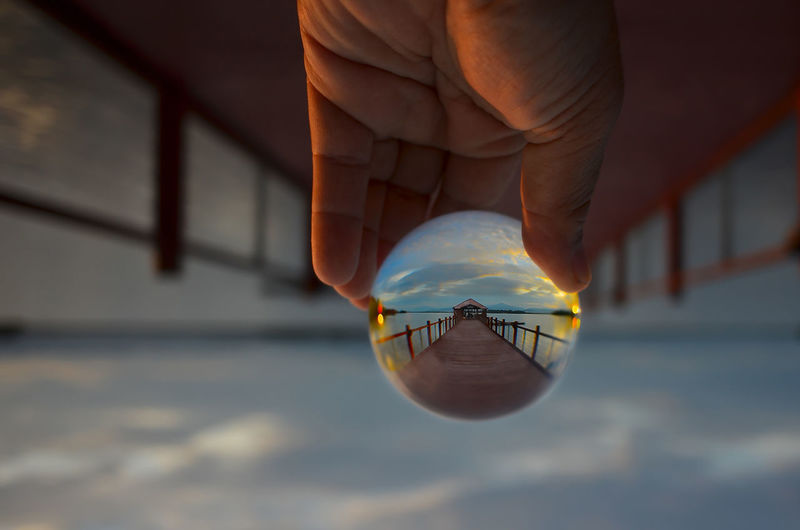 Close-up of person hand holding crystal ball on pier against cloudy sky during sunset