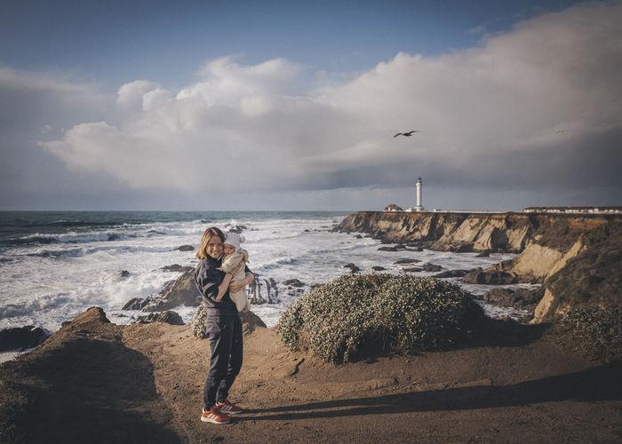 Man looking at sea shore against sky
