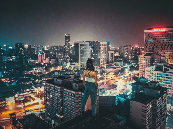 Rear view of woman looking at illuminated cityscape while standing on building terrace against sky