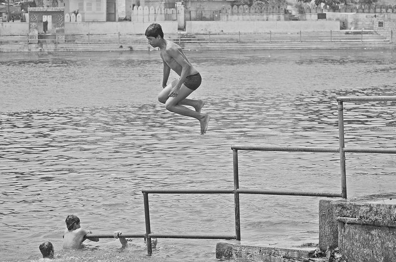 People jumping on pier over sea