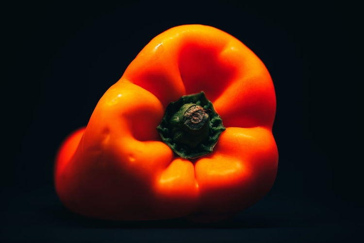 Close-up of orange bell peppers against black background