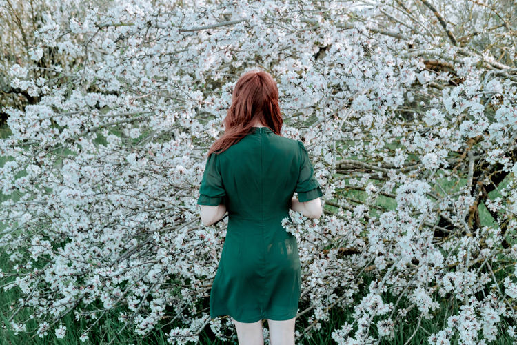 Rear view of woman standing by flower tree