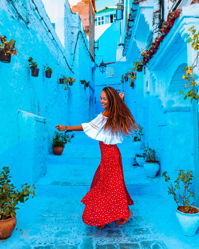 Girl in a red skirt dancing in the middle of the street in the blue city of chefchaouen in morocco