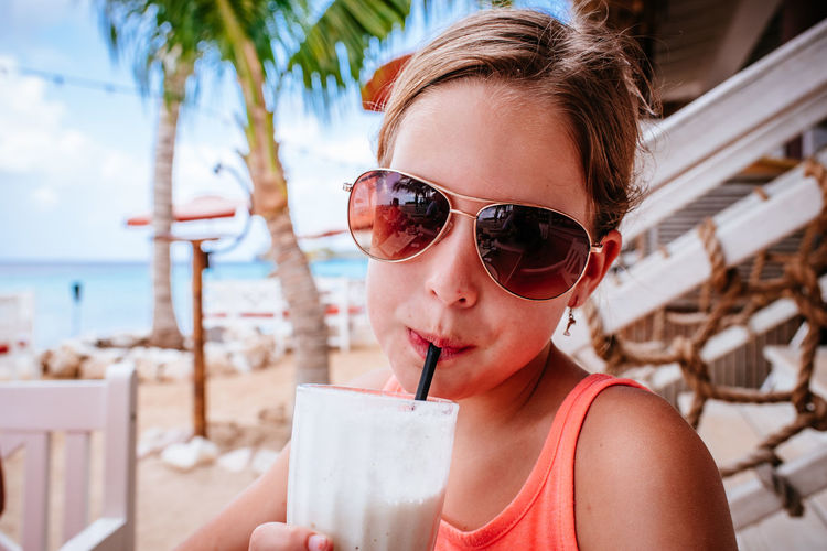 Portrait of girl drinking smoothie while standing at beach