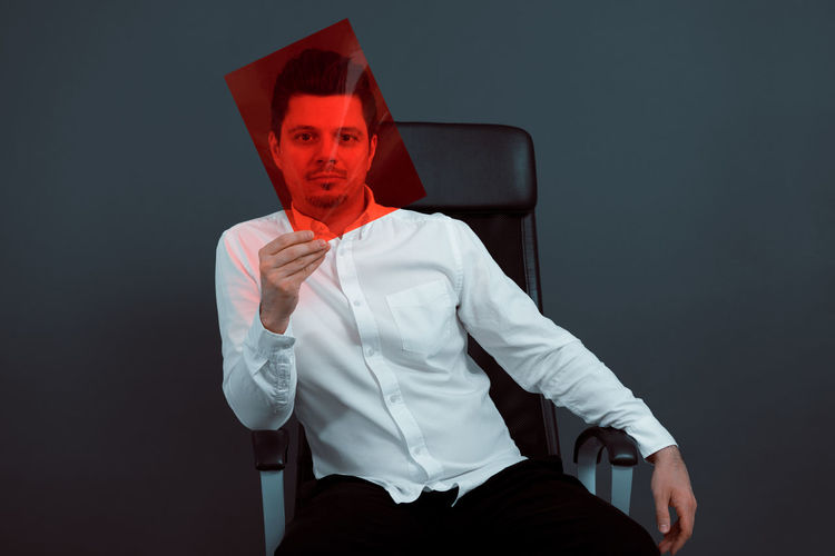 Red One Person One Man Only Men Portrait Studio Shot Sitting Looking At Camera Gray Background Business Black Background Disguise Tensed Overworked Exhaustion Frustration Emotional Stress Downsizing Anxiety  Hopelessness Tired Working Late Physical Pressure Worried