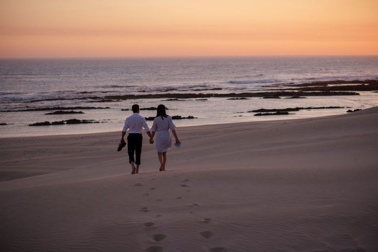 Rear view of couple walking on beach against sky during sunset