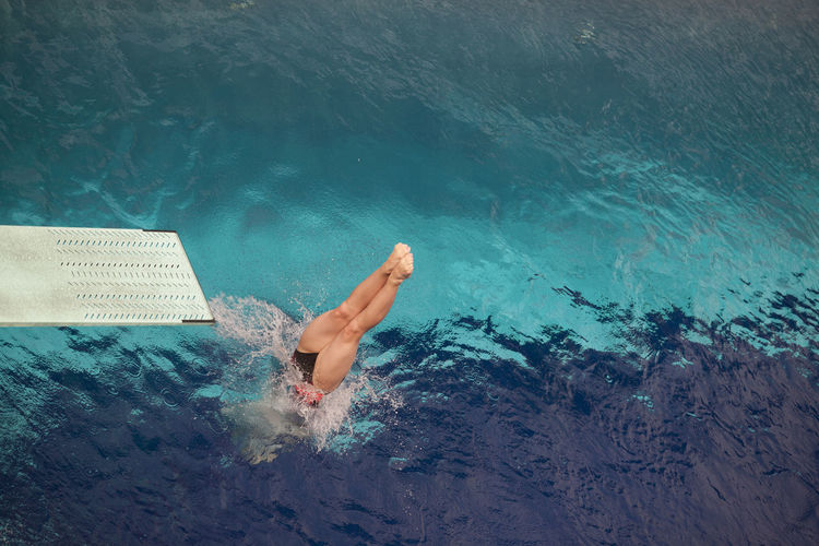 Jumping into the swimming pool. Into The Water Jump Springboard Jumping Activity barefoot Board Clear Blue Water Diver Diving Diving Into Water Motion Movement One Person Pool Splashing Sport Sports Springboard Springboard Diver Swimmer Swimming Swimming Pool Underwater Water Watersports