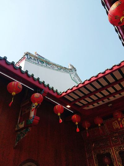 Low angle view of lanterns on building against clear sky