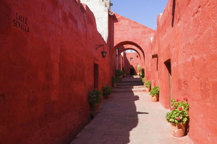 Monasterio De Santa Catalina This Is Latin America Arch Architecture Building Building Exterior Built Structure Day Footpath Narrow No People Potted Plant Red Shadow Sunlight Wall