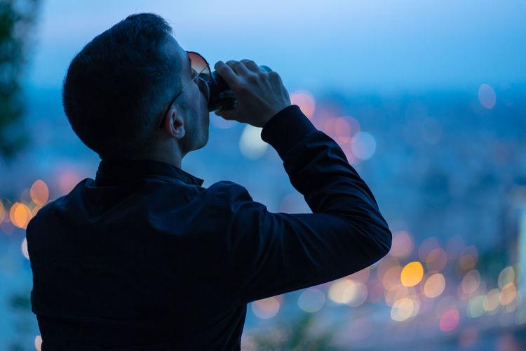 Rear view of man having drink at dusk