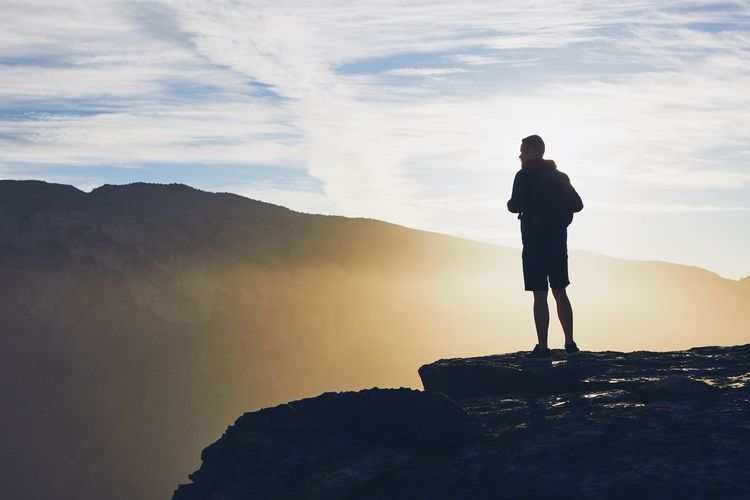 Man standing at cliff against sky during sunset