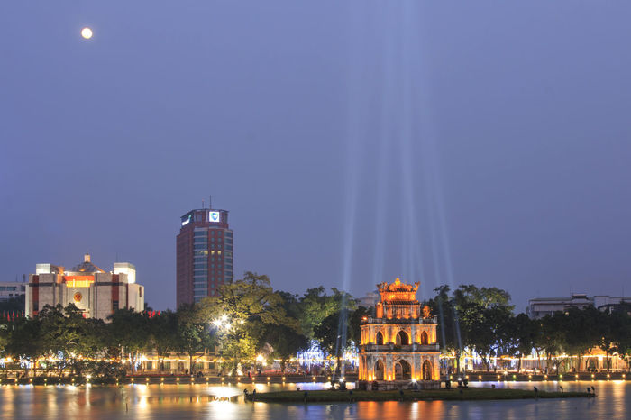 Hanoi, Vietnam - 21 February, 2016: Night view of the Hoan Kiem Lake (Lake of the Returned Sword) and the Turtle Tower with full moon. Architecture ASIA Blue Built Structure City Cityscape Hanoi Vietnam  Ho Chi Minh Mausoleum Hoan Kiem Lake Illuminated Landmark Modern Night One Pillar Pagoda People Reflection River Sky Skyscraper Tourists Traffic Traffic Jam Vietnam Water Waterfront