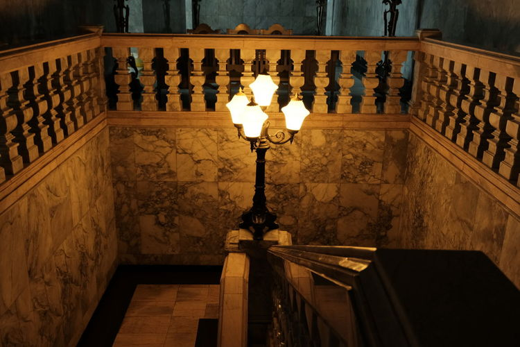 Low angle view of illuminated lamp on staircase by building