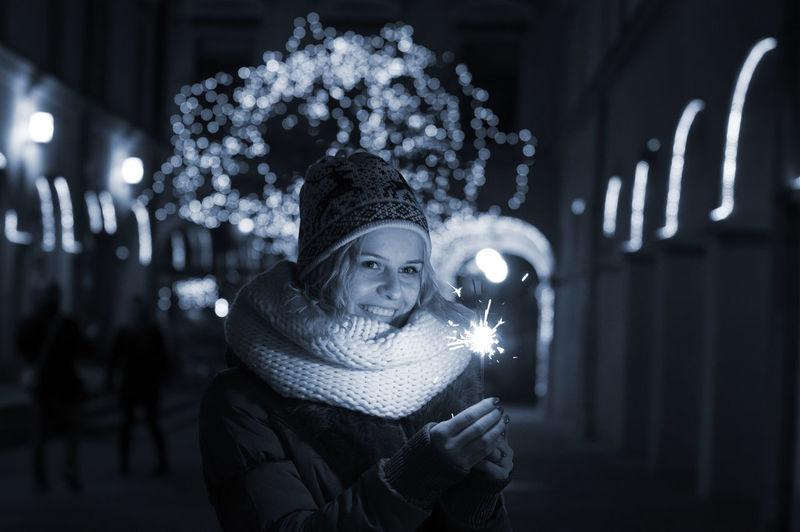 Smiling woman holding lit sparkler at night