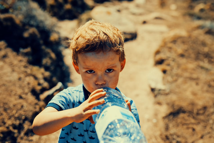 Portrait of boy drinking water at beach