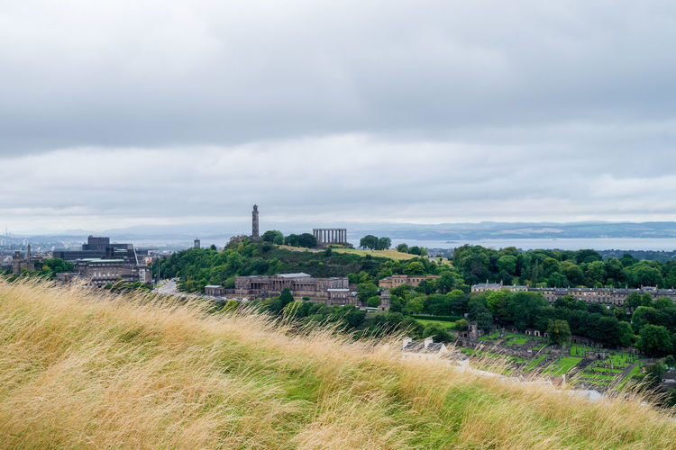 Yellow withered grass at Holyrood Park and Calton Hill & its monuments under cloudy sky. Attractions Autumn Brown Buildings Calton Hill Cloud Edinburgh Grass Holyrood Park Landscape Meadow Monument Season  Sky Travel Yellow