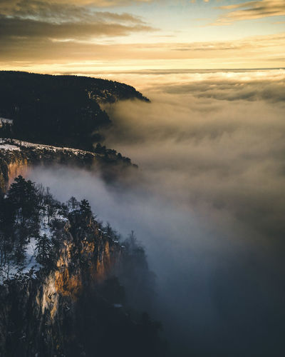 Scenic view of fog against sky during sunset