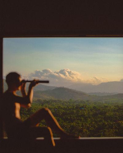 Defocused image of man looking at view through telescope against landscape
