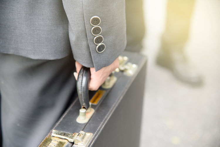 Midsection of woman holding briefcase standing outdoors