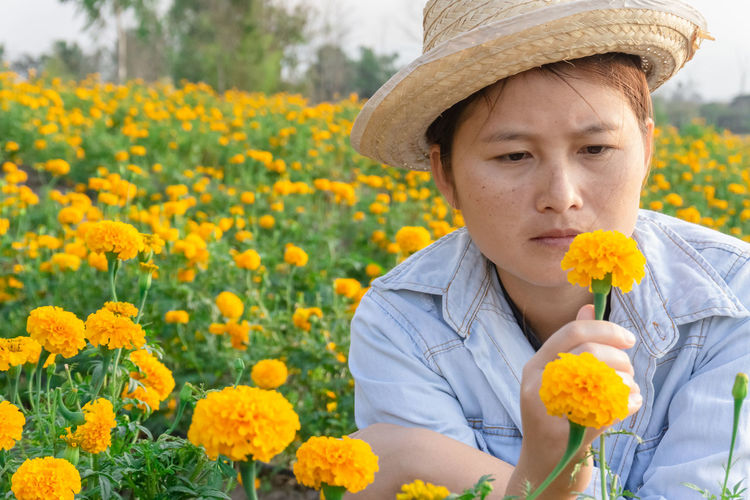 Marigold Portrait Flower Marigold Flower Farmer Selective Focus Lifestyles Outdoors Nature Plant Leisure Activity Care Check Yellow One Person Hat Flowering Plant Clothing Front View Beauty In Nature Growth Freshness Headshot Real People Fragility Day Vulnerability  Flower Head