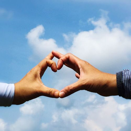 Cropped hands of couple making heart shape