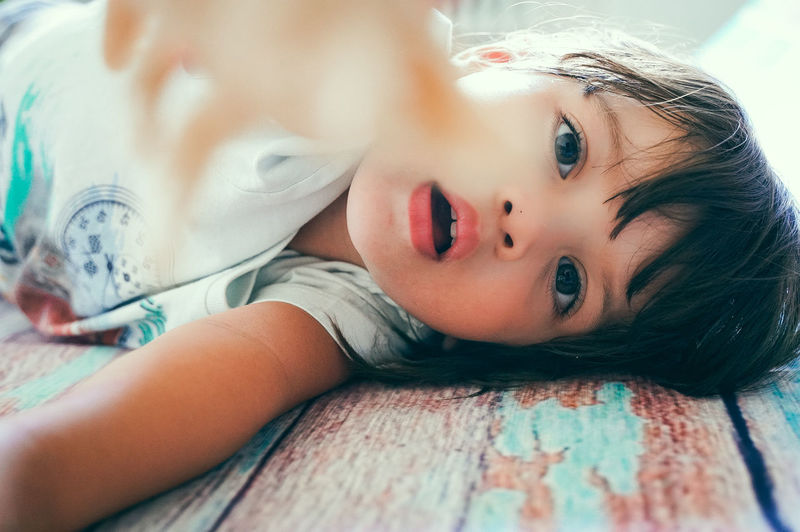 Close-up portrait of cute girl lying on bed