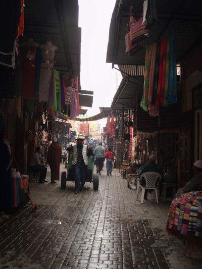 Africa Cart City Cobblestone Culture Fabric Market Marrakech Marrakesh Medina Morocco Overcast Reflection Sky Stone Textiles Urban Water Wet