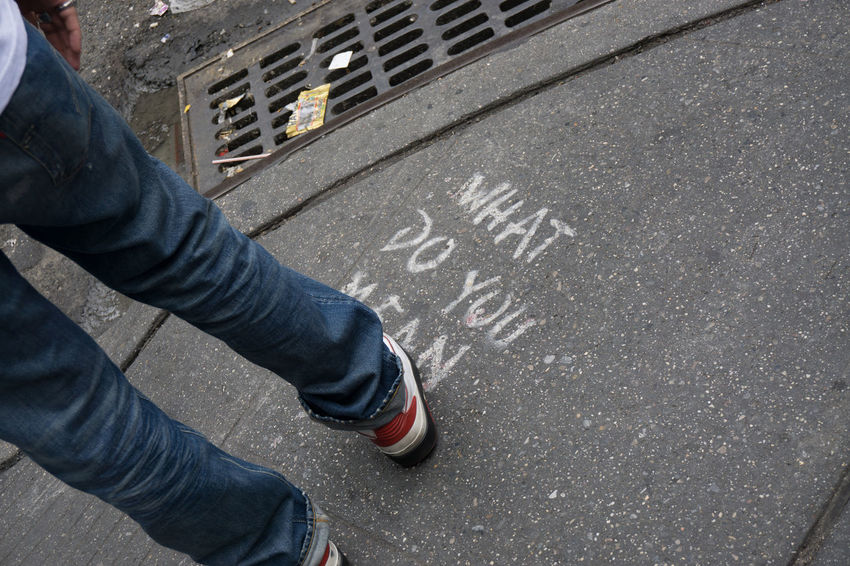 What do you mean (Words on Sidewalk) Chalk Fashion Human Leg Pavement Personal Perspective Phrase Shoe Sidewalk Standing Street Text What Do You Mean? Wording