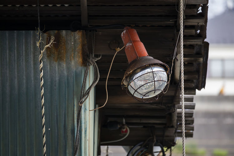 Low angle view of lighting equipment hanging on rope against building
