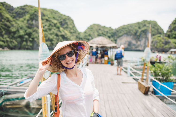 Vietnam Casual Clothing Curly Hair Day Fashion Focus On Foreground Front View Girl Glasses Ha Long Bay Hairstyle Hat Incidental People Leisure Activity Lifestyles Looking At Camera Nature One Person Outdoors Portrait Real People Smiling Sunglasses Water Women Young Adult Moments Of Happiness