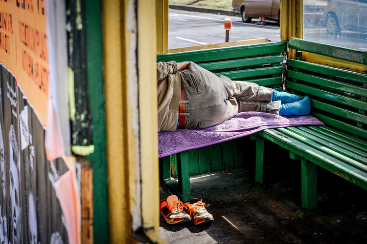 Low section of man sleeping on bench