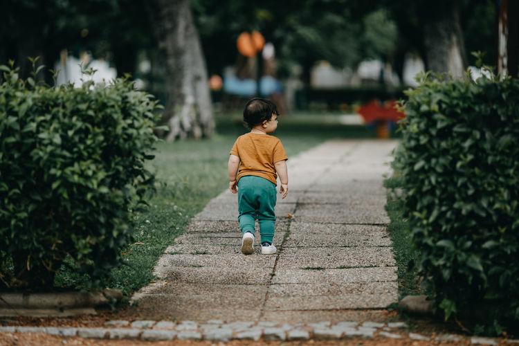Rear view of boy walking on footpath