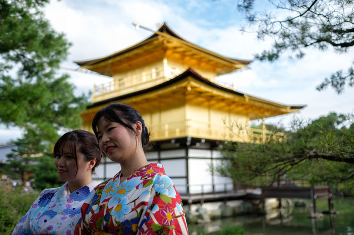 Kyoto Architecture Building Exterior Built Structure Casual Clothing Culture Day Elementary Age Focus On Foreground Gold In Front Of Kinkaku-ji Leisure Activity Lifestyles Low Angle View Outdoors Person Place Of Worship Sky Spirituality Tourism Tree Vacations Young Adult