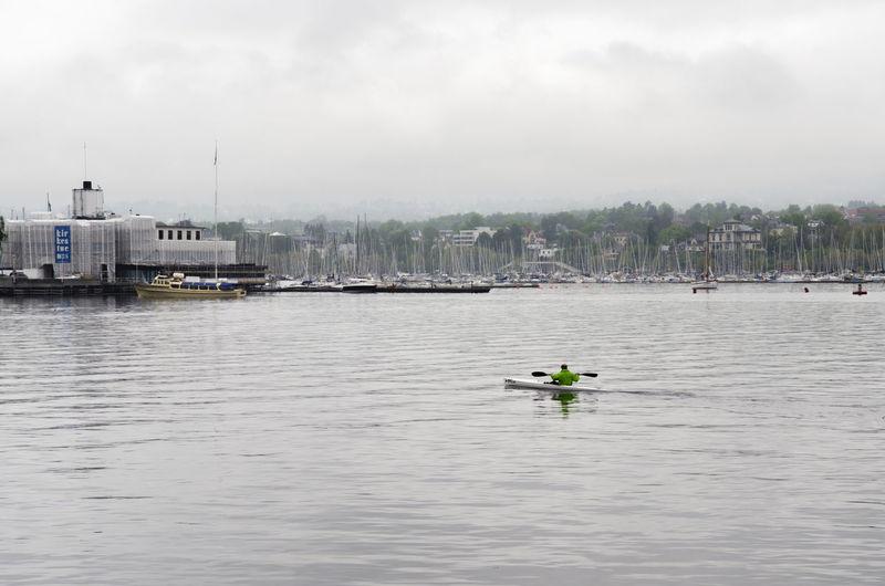 Rear view of man kayaking in river against sky