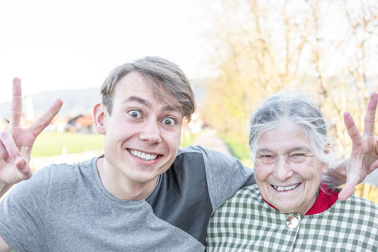 Portrait of happy grandmother with grandson gesturing against clear sky