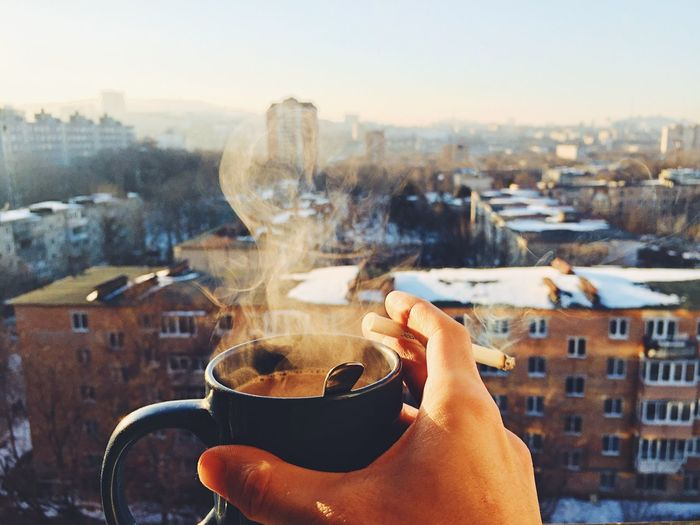 Cropped hand holding coffee cup and cigarette against cityscape