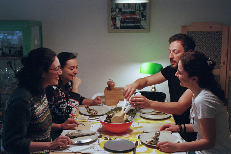 Happy friends having dinner at home