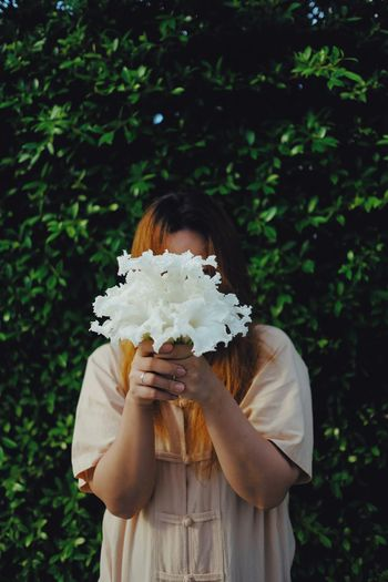 Woman Showing White Flowers While Standing Against Plants