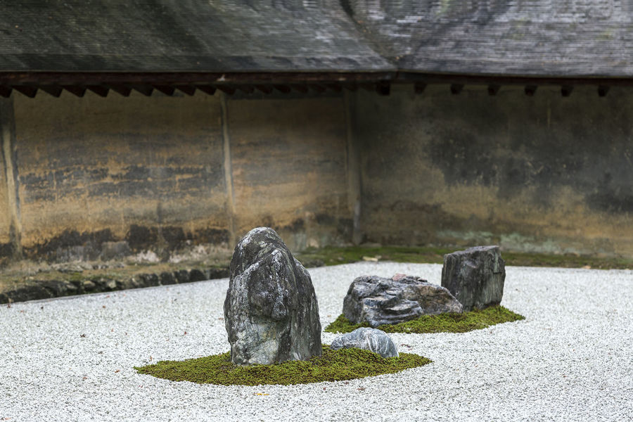 Zen Rock Garden in Ryoan-ji a garden fifteen stones on white gravel, Kyoto, Japan Japan Ryoan-ji Temple Architecture Art And Craft Built Structure Concrete Creativity Kyoto No People Outdoors Representation Rock Rock - Object Sculpture Solid Stone Stone Material Wall - Building Feature Zen Garden Zen Rock Garden Japanese