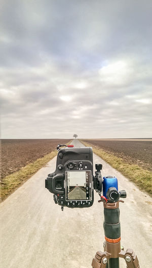Agriculture Camera - Photographic Equipment Cloud - Sky Clouds And Sky Day Field Leading Lines Nature No People Outdoors Photography Themes Picture In Picture Road Rural Scene Sky Symmetry Technology Tree Tripod Photography