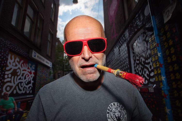 Portrait of man smoking cigarette in city