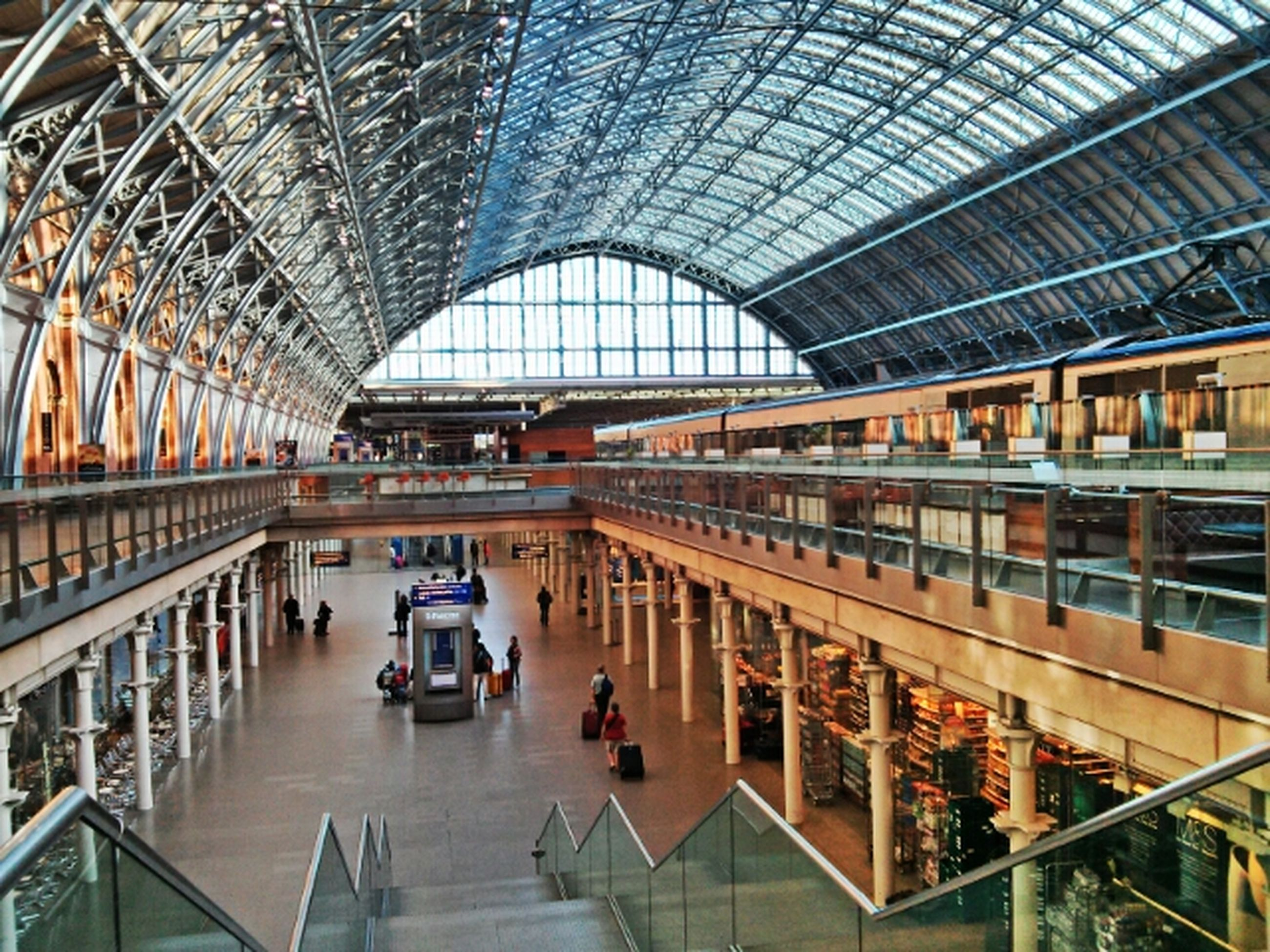 indoors, architecture, built structure, incidental people, lifestyles, transportation, men, person, travel, modern, railing, ceiling, high angle view, leisure activity, railroad station, shopping mall, large group of people, city life, public transportation