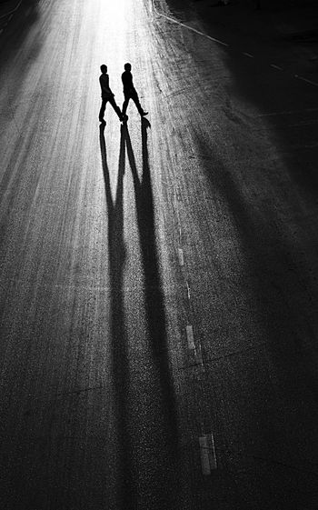 High angle view of silhouette men crossing road at night