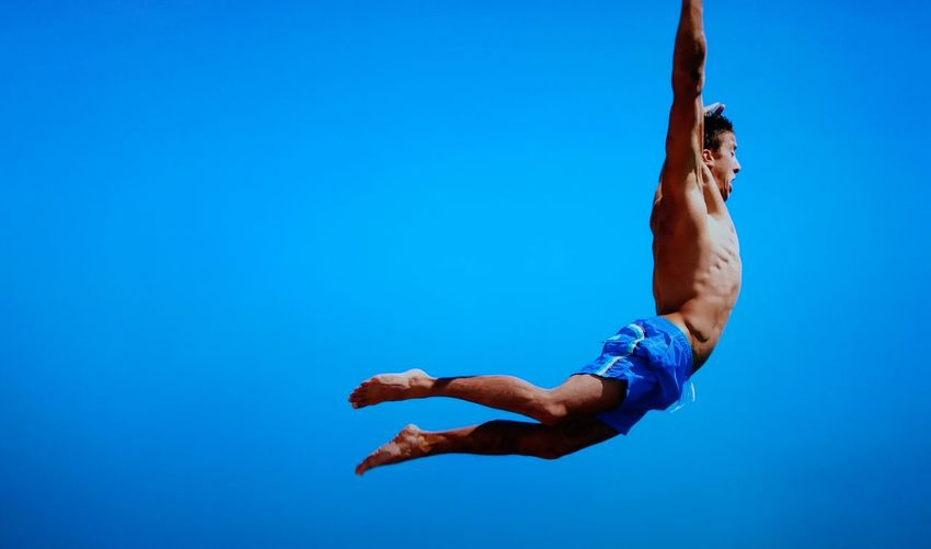 Shirtless Man Jumping Against Clear Blue Sky