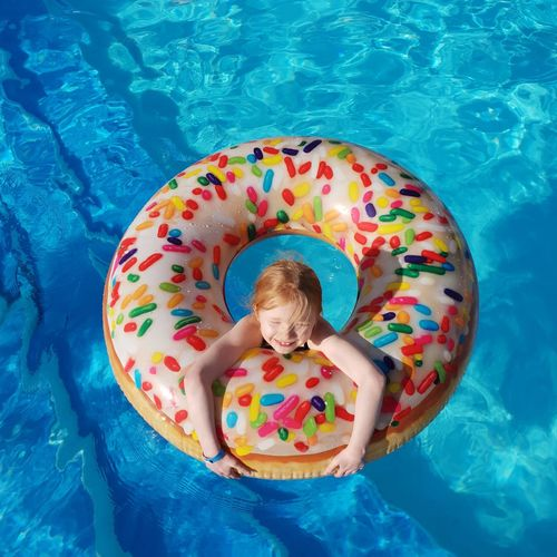 High angle view of smiling girl with inflatable ring in swimming pool