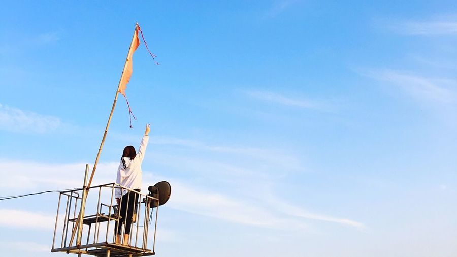 Low Angle View Of Woman Standing On Lookout Tower